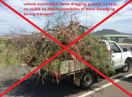 vehicle overloaded, items dragging ground, no tarp, no visible tie down, possibility of items dislodging during transport